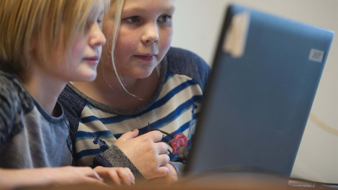Twee leerlingen kijken naar het beeldscherm van een laptop