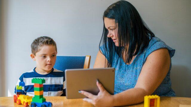 Leraar geeft les aan een leerling met een verstandelijke beperking