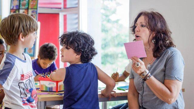Leraar leest kaartje voor aan leerling op basisschool
