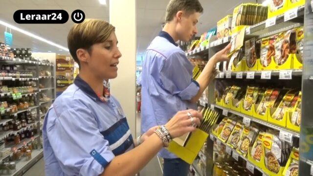 Een stagecoördinator leert een stagiaire vakken vullen in een supermarkt