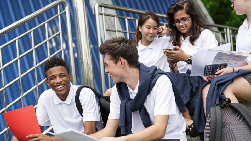 Leerlingen met verschillende achtergronden zitten met elkaar te lachen op de trap
