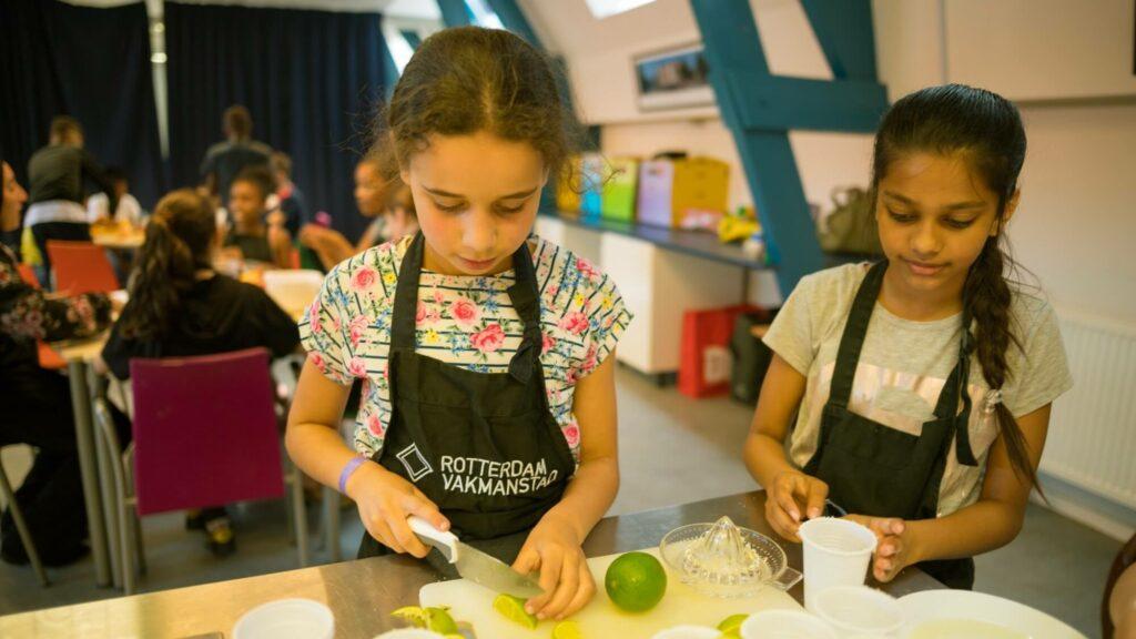 Twee meisjes zijn aan het koken, de linker snijdt een limoen.