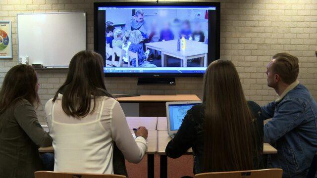 Vier studenten bekijken videobeelden van een les en geven feedback.
