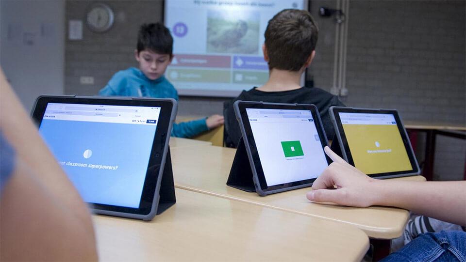 Leerlingen in het po zitten rond de tafel met tablets voor hen
