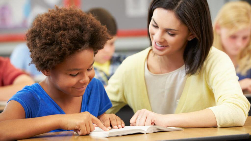 Lerares wijst iets aan in het boek van de leerling