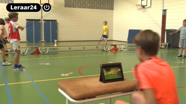 Jongetje kijkt na een springoefening zijn eigen bewegingen terug op een tablet tijdens de gymles