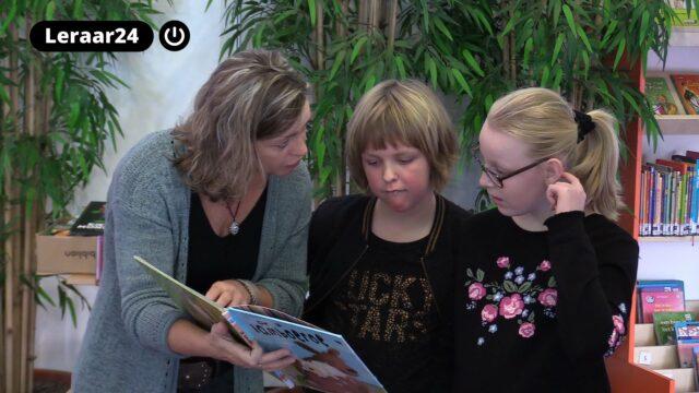 leraar leest aan twee leerlingen voor