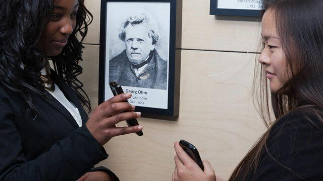 Twee vo leerlingen laten elkaar hun smartphone zien