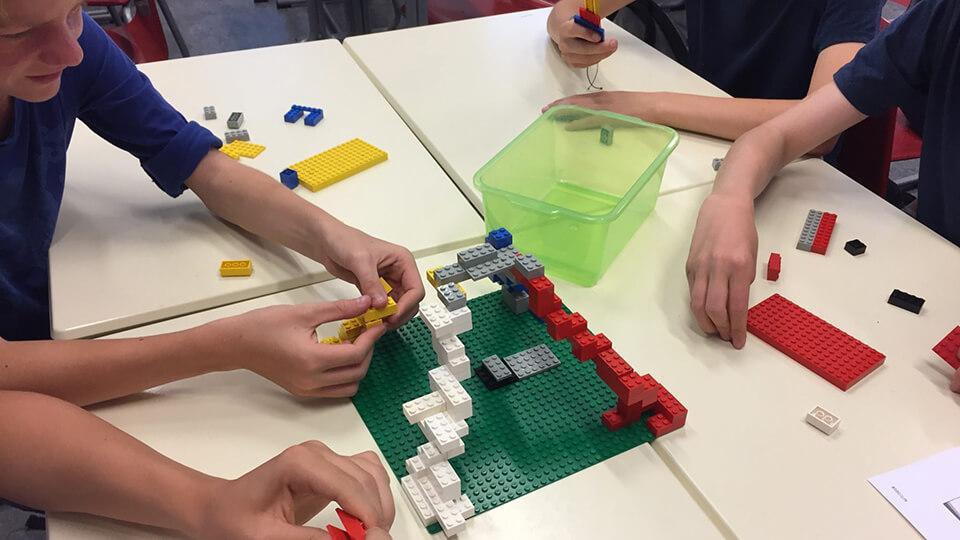 Handen van leelringen die een atoommodel van lego maken