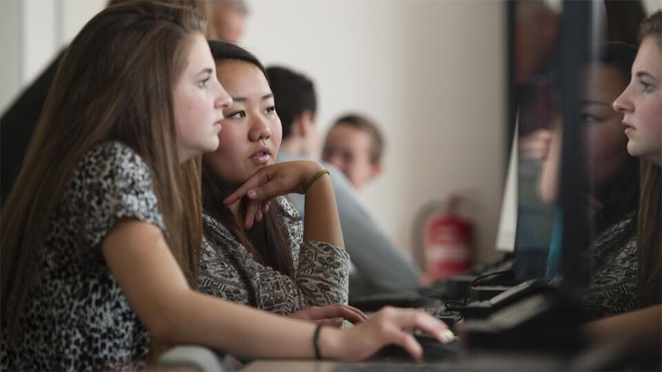Twee leerlingen zitten achter een computerscherm