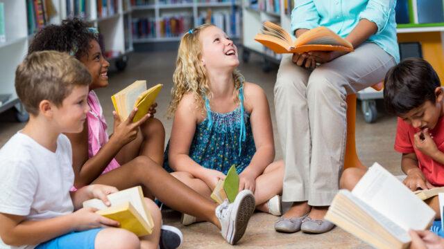 Kinderen zitten in een kring met een boek op schoot
