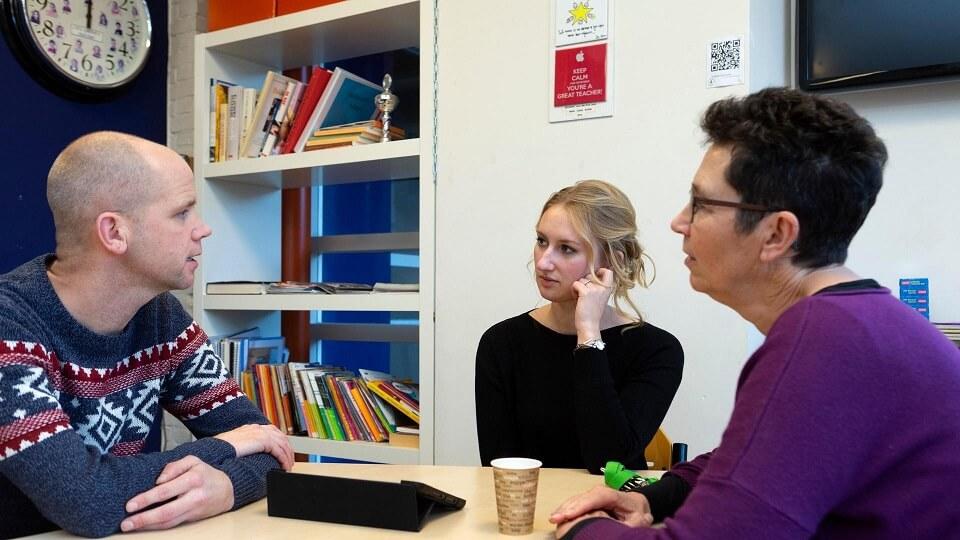 Een leraar is aan een tafel in gesprek met ouders