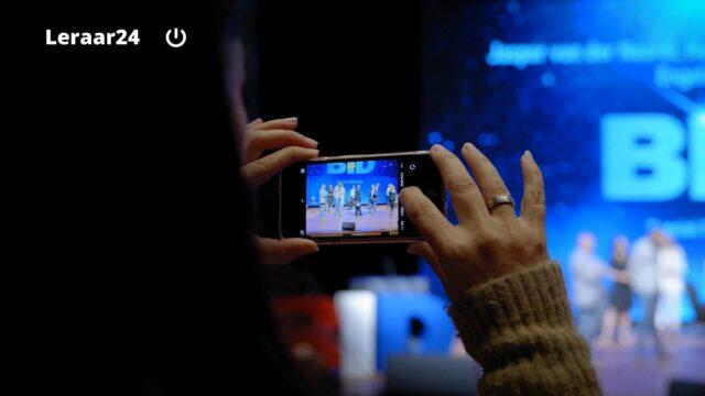 Vrouw maakt foto met smartphone van leraren van het jaar 2021 op het podium