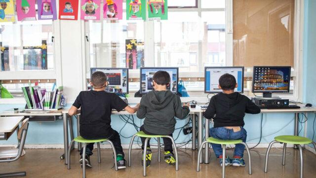 Drie jongens werken achter een computer in de klas