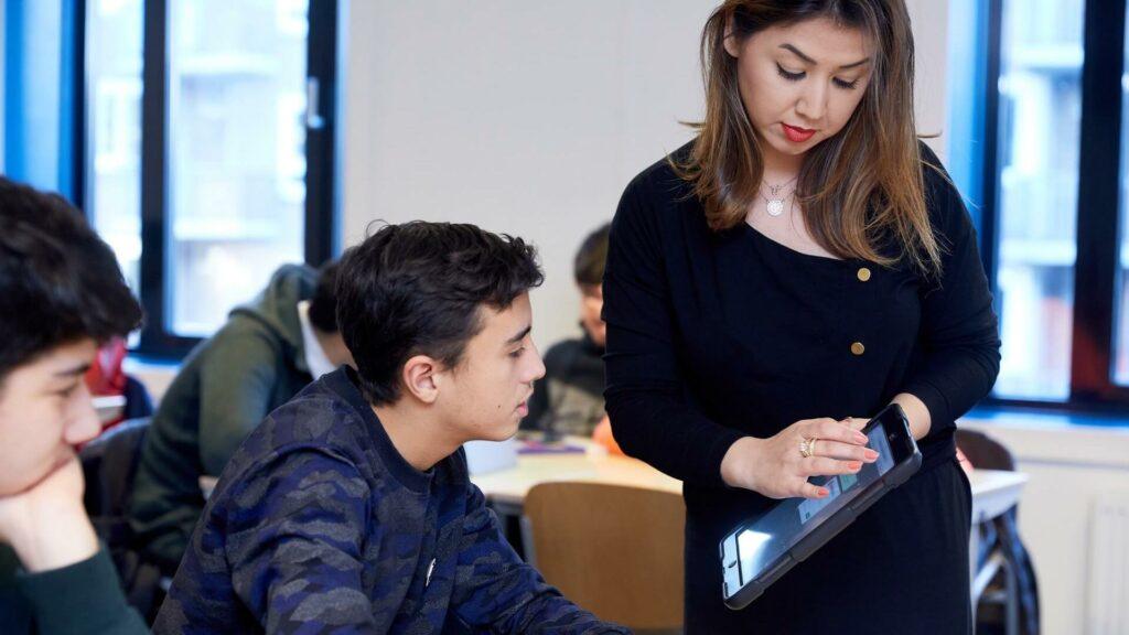 Een docent geeft twee leerlingen uitleg op een tablet.