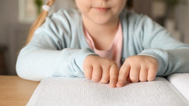 Leerling met visuele beperking leest met braille een boek