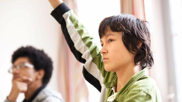 Een jongen steekt zijn vinger op in de klas