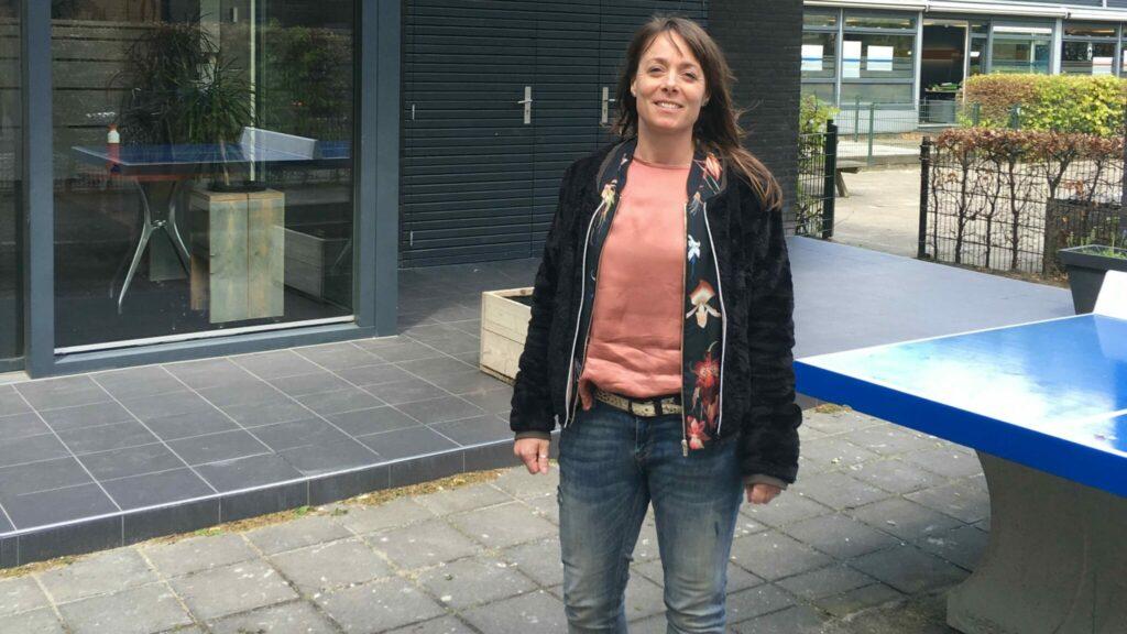 Gymleraar Linda staat naast een tafeltennistafel voor de school.