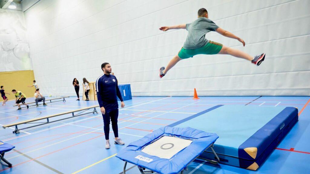 Een leerling springt wijdbeens van de trampoline terwijl de gymdocent toekijkt.