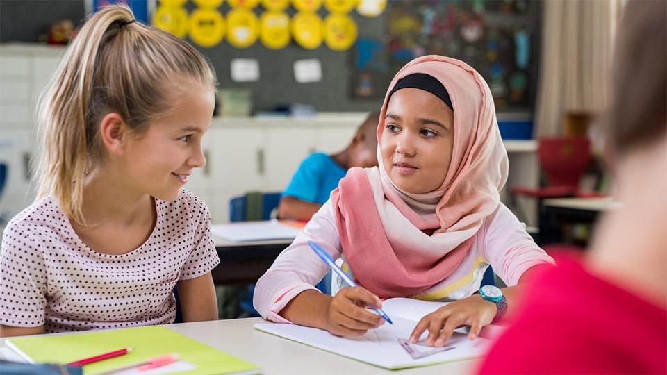 Een blond meisje werkt samen met een meisje met een hoofdddoek.