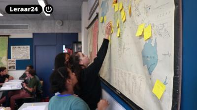 Leerlingen plakken memobriefjes met geschiedenisonderwerpen op een wereldkaart