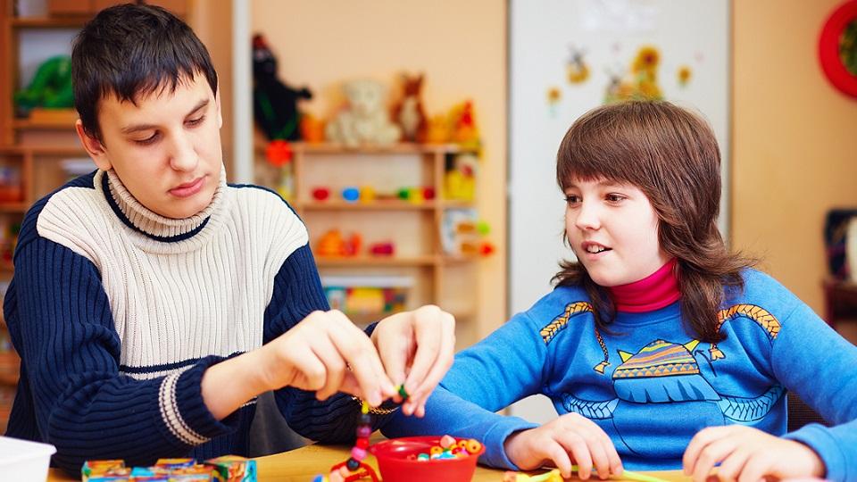 Twee autistische leerlingen spelen samen met kraaltjes