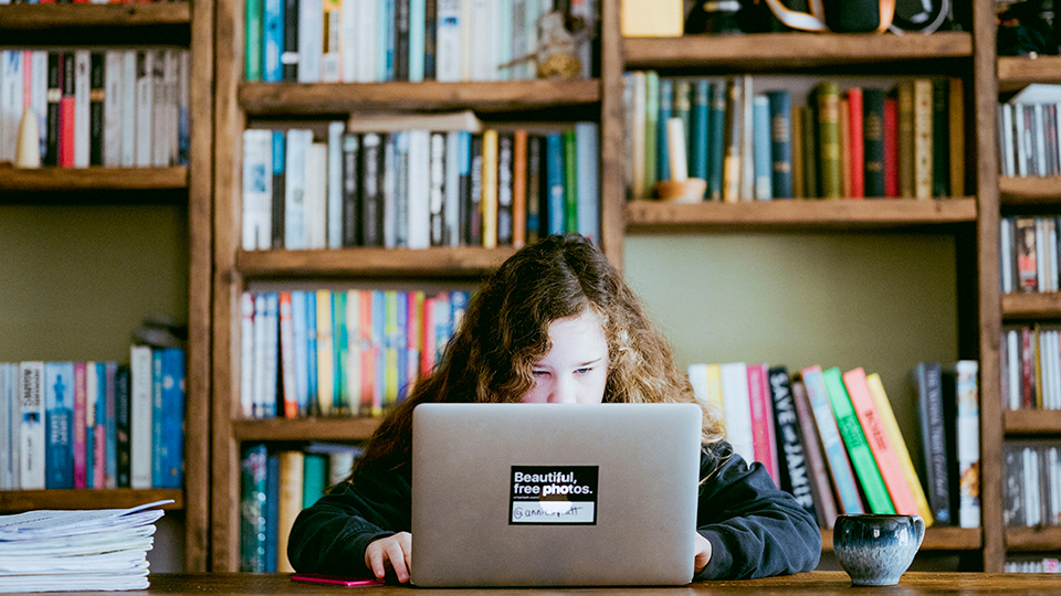 Meisje werkt thuis aan tafel aan schoolwerk