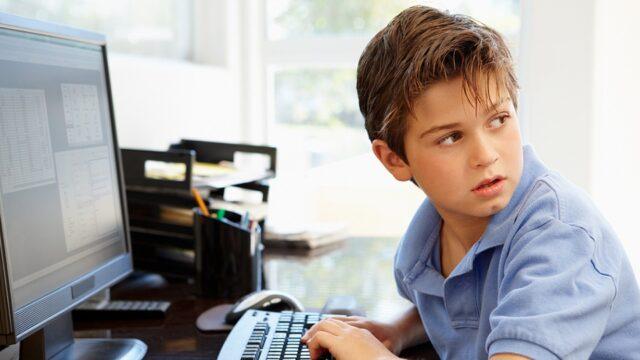 Jongetje werkt thuis achter zijn pc