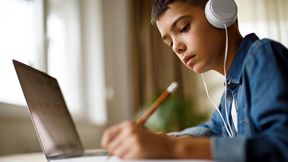 Leerling zit achter een laptop met een koptelefoon op en schrijft iets op papier