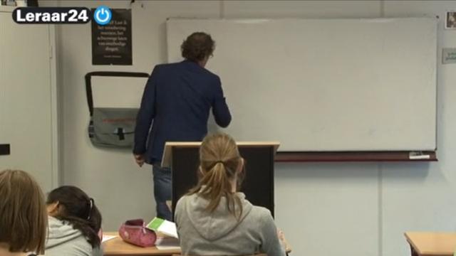 Een leraar schrijft iets op het bord, terwijl zijn leerlingen in de klas toekijken