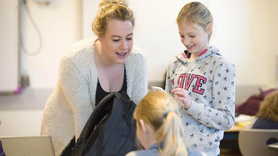 Lerares praat mer 2 leerlingen, een leerling houd smartphone vast