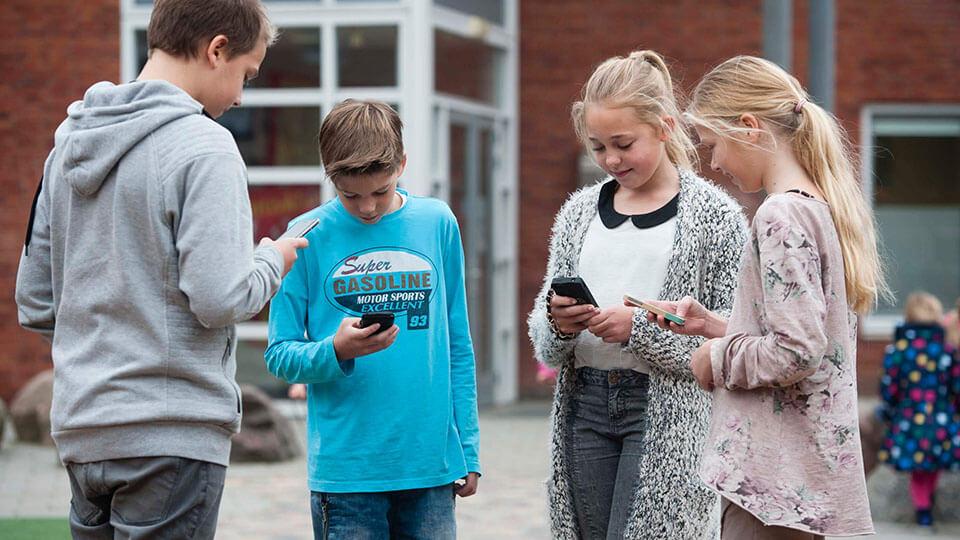 Leerlingen po staan in een kringetje op het schoolplein en kijken op hun smartphone