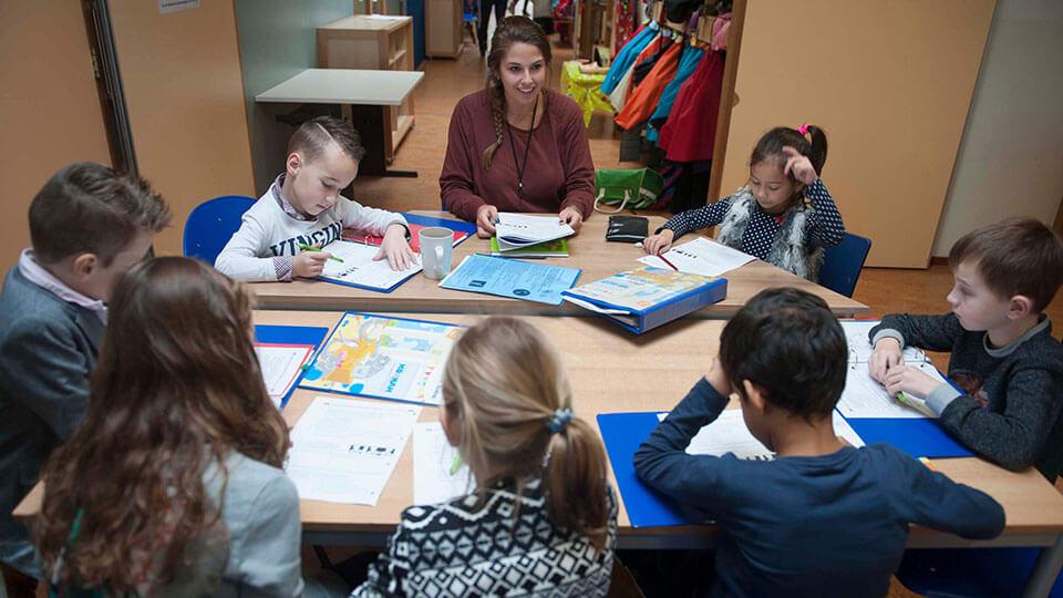 Lerares zit met leerlingen po rond de tafel