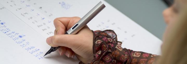 Een leerling schrijft in een werkboek.