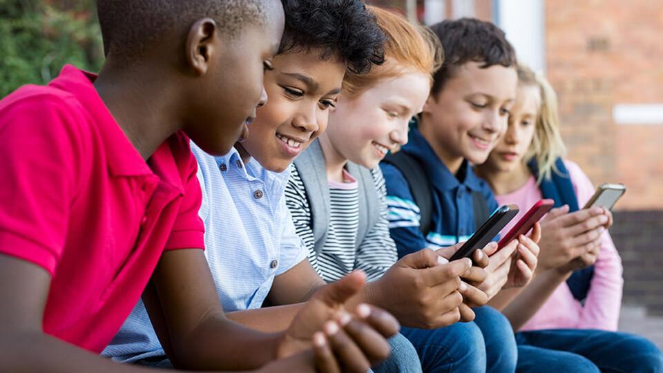 Vijf leerlingen zitten buiten op een rij en kijken op hun smartphones