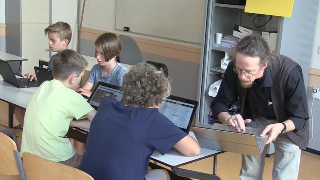 Leraar staat aan het bureau van een aantal leerlingen met een laptop. Hij legt iets aan ze uit.