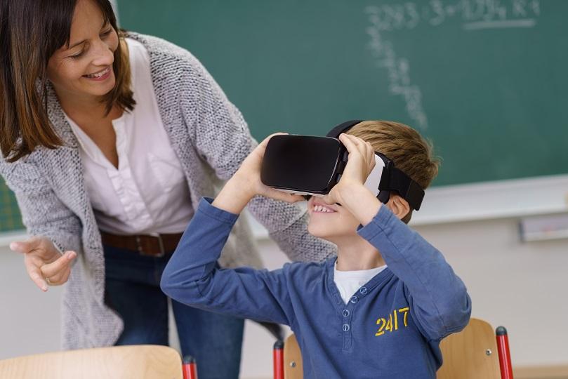 lerares begeleidt jongen die door VR-bril kijkt