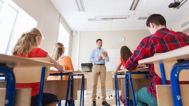 Leraar geeft les aan leerlingen uit het voortgezet onderwijs