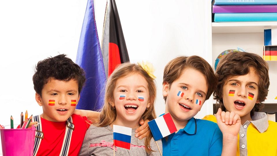 Vier leerlingen met verschillende vlaggen geschminkt op hun gezicht krijgen les in vreemde talen.