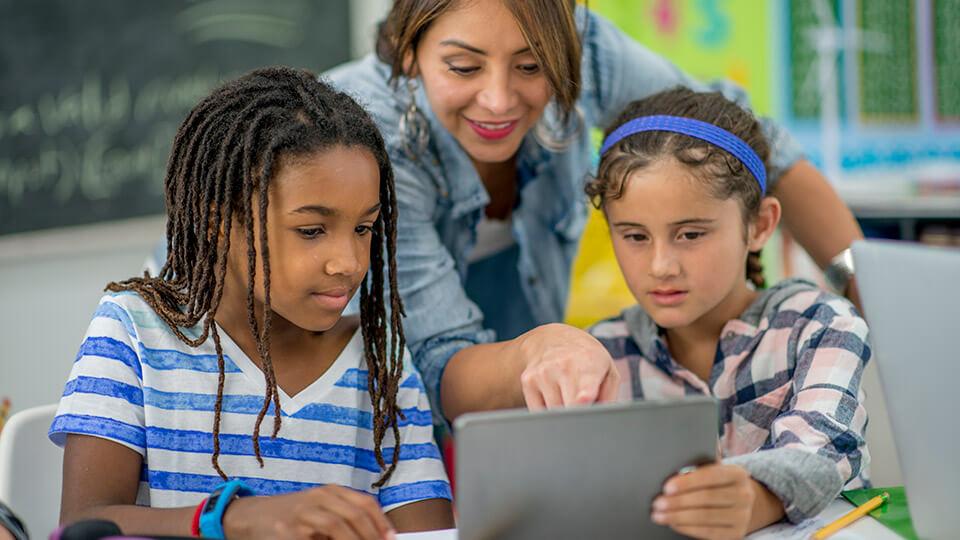 Lerares wijst naar tablet waar twee meisjes mee werken.