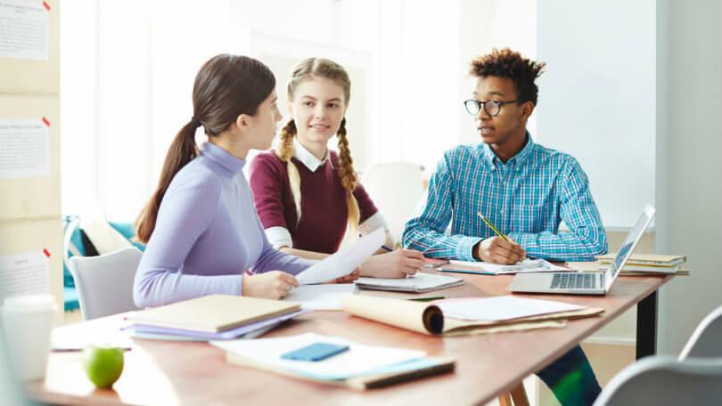 drie leerlingen overleggen tijdens zelfstandig werk
