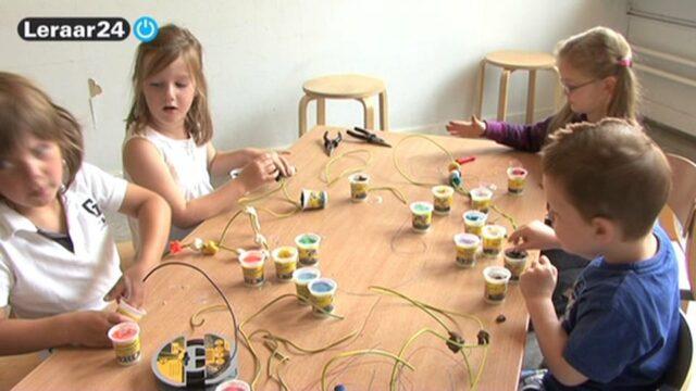 Vier kleuters zijn aan een tafel bezig met staaldraad en klei.