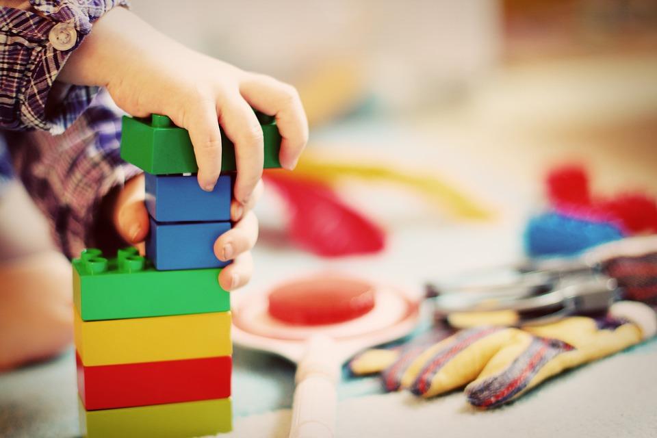 Een leerling bouwt een toren van legoblokjes, een vorm van spel.