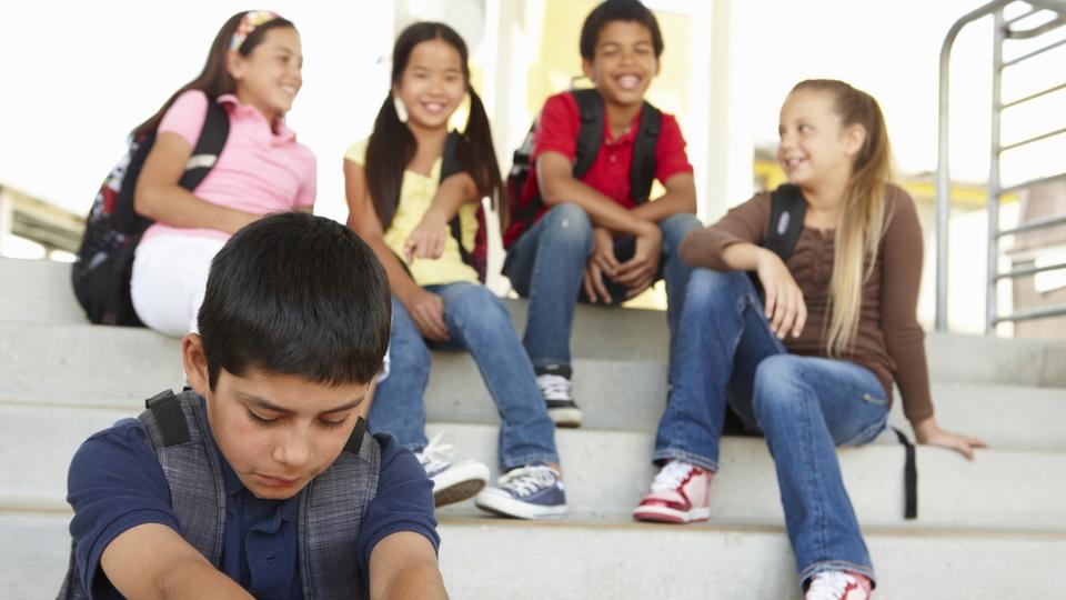 Leerlingen lachen met elkaar en sluiten een medeleerling buiten