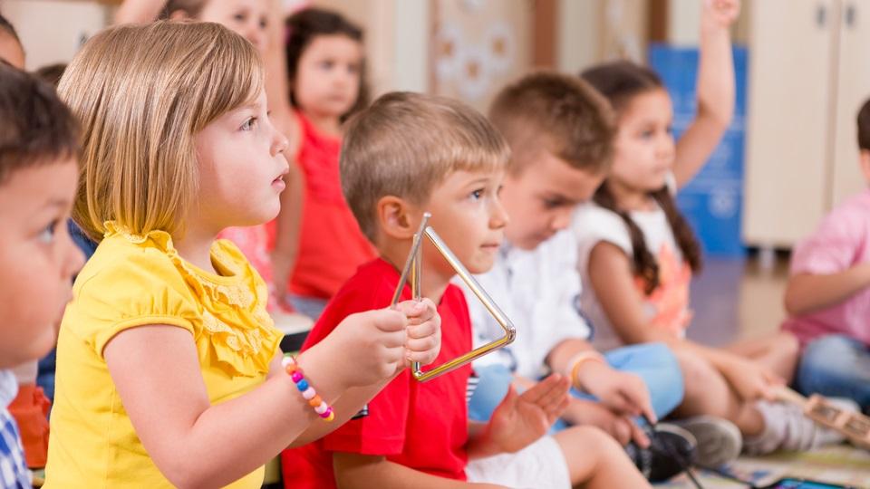Kinderen hebben muziekles in de klas