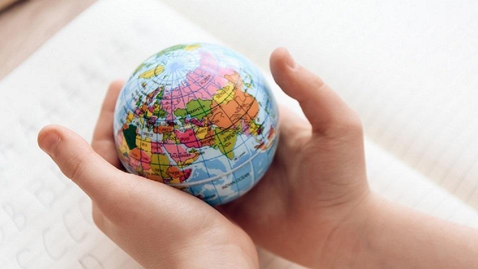 kinderhanden houden kleine wereldbol vast