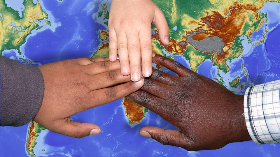 Drie kinderen leggen hun hand op een wereldbol