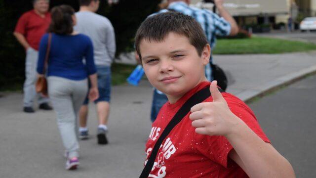 Een leerling staat op het schoolplein en steekt zijn duim omhoog.