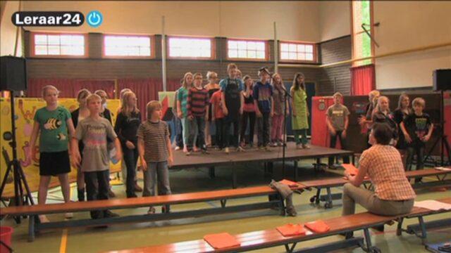Een groep 8 staat op het podium voor het oefenen van de musical.