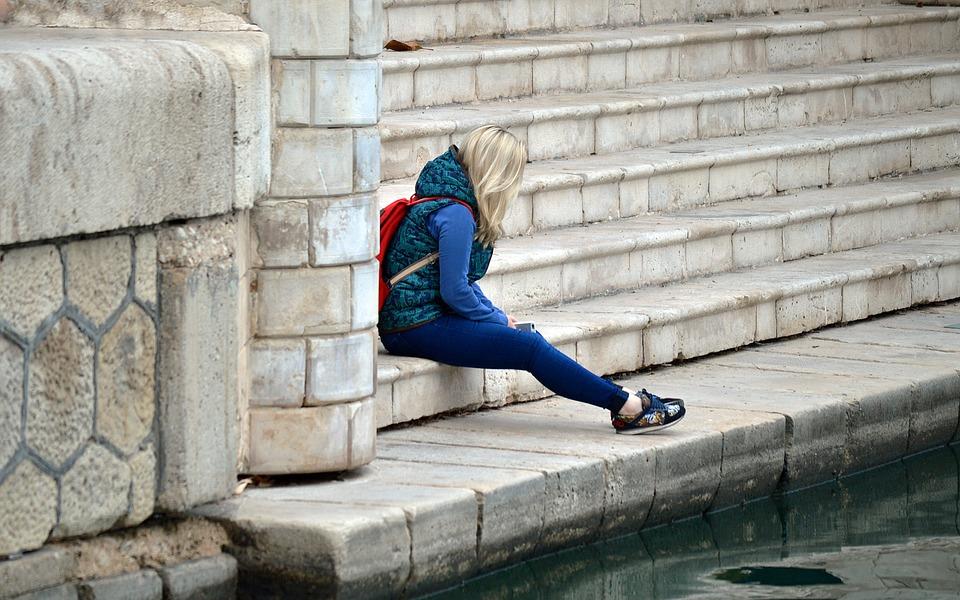 Een meisje zit buiten alleen op een stoepje.